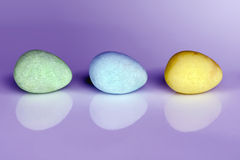 Fun Easter eggs in a row. Pastel colored Easter egg candy in a row on purple background with reflection and copy space for your text Stock Images
