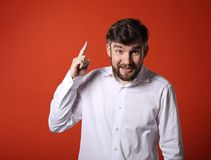 Fun emotional bearded smiling man thinking and have an idea hold. Ing and showing the finder up on empty copy space orange background Stock Photography