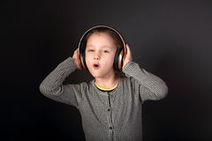 Fun emotional grimacing kid girl listening the music in wireless Royalty Free Stock Image