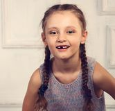 Fun emotional kid girl without milk tooth posing in fashion blou. Se and braid hairstyle in studio wall background. Closeup toned portrait Stock Photo