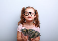 Fun emotional small kid girl in glasses holding and showing doll Stock Images