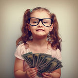 Fun emotional small kid girl in glasses holding and showing doll Royalty Free Stock Images
