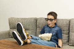 Fun excited boy in 3D glasses watching TV with popcorn and remo control in the living room stock image