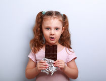 Fun expression kid girl eating dark chocolate and looking happy. Stock Images