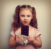 Fun expression kid girl eating dark chocolate and looking happy. Royalty Free Stock Images