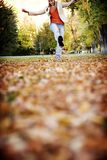Fun in fall. Young woman kicking in the leaves in fall Stock Photos