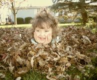 Young Girl Laying in Fall Leaves Royalty Free Stock Photography
