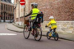 Fun family bike riding with protective gears and fluorescent vests
