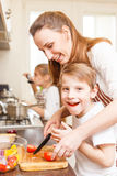Fun family cooking. Son with mother cut tomatoes royalty free stock photo