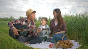 Fun family vacation, merry male plays musical instrument while woman with child sing and clap while relaxing on picnic. Outdoors in green field close-up stock video footage