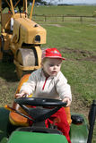 Fun on the Farm. Toddler playing on a small farm tractor Royalty Free Stock Photo