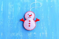 Fun felt Christmas snowman ornament isolated on a blue wooden background. How to make a Christmas snowman ornament. Step Royalty Free Stock Photo