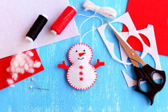 Fun felt Christmas snowman ornament, scissors, thread, needle, pins, cord, felt pieces and scraps on wooden background Stock Photos