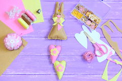 Fun felt Easter bunny with hearts decoration. Sewing supplies on a wooden table. Modern bunny wall decor. Easter craft projects Stock Images