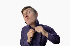 Fun fishye a look on young businessman who tries to tie one's tie on white background Royalty Free Stock Photos