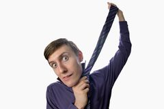 Fun fishye a look on young businessman who tries to tie one's tie on white background Stock Photography