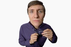 Fun fishye a look on young businessman who tries to tie one's tie on white background Royalty Free Stock Image