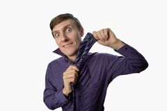 Fun fishye a look on young businessman who tries to tie one's tie on white background Stock Image