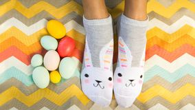 Fun Flat Lay of person wearing bunny socks with Easter eggs. bla royalty free stock image