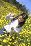 Fun with flowers 2. Little girl picking up yellow daisies Royalty Free Stock Photos