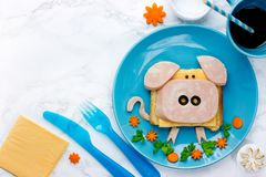 Fun food art idea for kids breakfast - funny pig sandwich. With cheese, ham and olives on blue plate top view royalty free stock photo