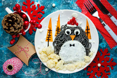 Fun food art idea for kids - penguin black spagehetti with fried Stock Images