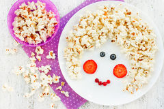 Fun food art idea for positive food with popcorn and berries. Gi Stock Images