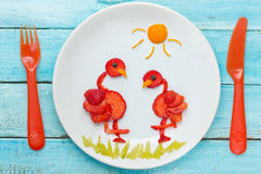 Fun food art strawberry flamingo. On plate stock images