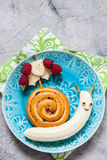Fun food. Cinnamon bun with banana look like a snail Stock Photos