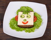 Fun food for kids - face on bread. Made from cheese, lettuce, tomato, cucumber and pepper Stock Images