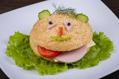 Fun food for kids - hamburger looks like a funny muzzle Royalty Free Stock Photography