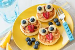 Fun food for kids. Pancakes with funny animal faces on colorful plate. Fun food for kids. Pancakes with funny animal faces on colorful yellow plate. Kids meal stock image