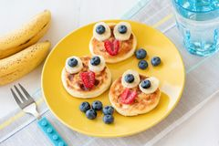 Fun food for kids. Pancakes with funny animal faces on colorful plate. Fun food for kids. Pancakes with funny animal faces on colorful yellow plate. Kids meal stock images