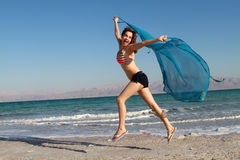Fun freedom girl. Beautiful girl jumping on the beach with USA bathing suit stock photography