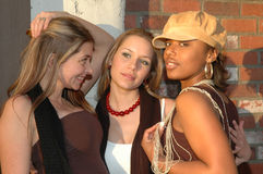 Fun Friends. City Fashion women standing in front of a brick wall. Friends hanging out laughing and having fun Stock Photos