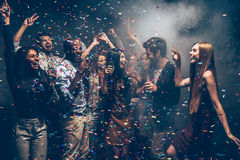 Fun and fun again. Group of beautiful young people throwing colorful confetti and looking happy Royalty Free Stock Image