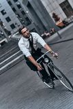 Fun and functional. Handsome young man in full suit looking forward while cycling outdoors Royalty Free Stock Photos