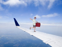 Fun and Funny Tourist Travel Flying on Airplane Jet Wing. Travel concept with a fun and funny tourist who likes to travel is flying on an airplane jet wing Royalty Free Stock Photos