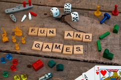 `Fun and Games` made from Scrabble game letters. Risk, Battleship pieces, Monopoly, Settler of Catan and other game pieces royalty free stock photos
