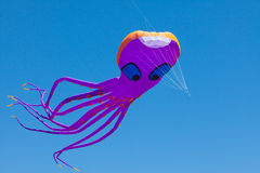Fun, giant purple octopus kite, 100 feet long, flying under blue sky Royalty Free Stock Image