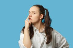 Show pig snout. Fun girl on blue background show pig snout gesture royalty free stock image