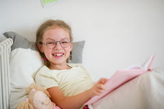 Fun girl in glasses and pigtails reads a book while lying in bed. Royalty Free Stock Image