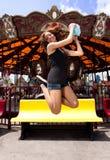Fun girl jumping at Carousel stock photo