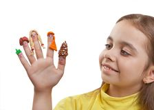Fun girl looking for a hand with the painted men on the fingers in plasticine wigs. Children`s art from clay on the fingers. Isolated on a white background Stock Photo