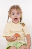 Fun girl opened her mouth while eating a muffin Royalty Free Stock Photos