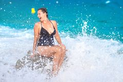 Fun girl on sea beach with splashes of water from waves. Young woman in bikini sits on beach. Girl bathing in sea royalty free stock photography
