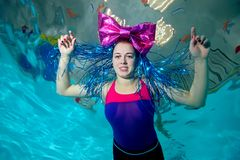 Fun girl swims underwater in the pool, arms outstretched to the sides, with a big red bow on her head, looks at camera and smiling. Portrait. Horizontal Stock Photos