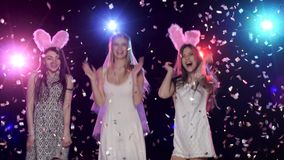 Fun girls at bachelorette party dancing and kiss the bride. Fun girls at bachelorette party dancing and kiss bride, against disco lights, glitter confetti. Bride stock video footage
