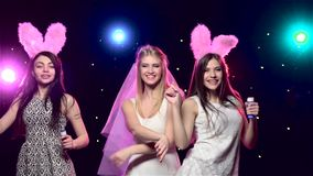 Fun girls at bachelorette party dancing. Slow motion. Fun girls at bachelorette party dancing, against disco lights, glitter confetti, bride with veil stock footage