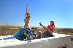 Fun Girls in Convertible. Attractive pretty happy party girls riding in a convertible with the top down out on a  country road. Shallow depth of field Royalty Free Stock Images